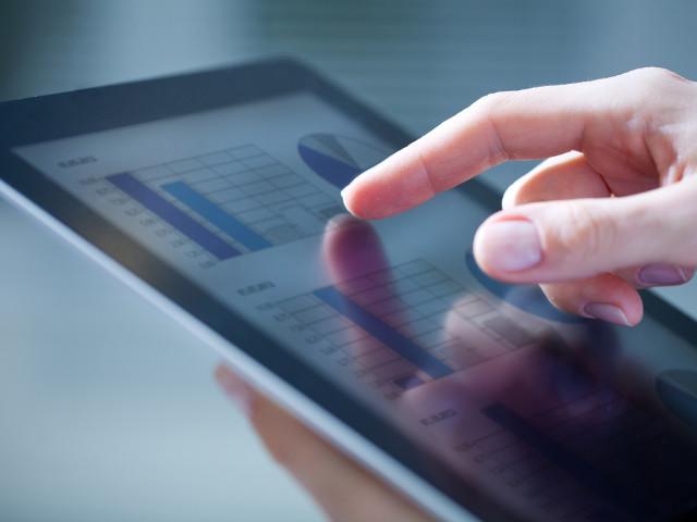 Człowiek oglądający wykresy na tablecie - usługi informatyczne dla firm PROTEUSS